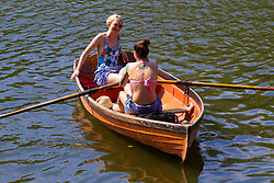 Two women enjoy the sunshine on the cool waters of the River Thames in Richmond as temperatures soar past the mid-30s in London. London, July 25 2019.