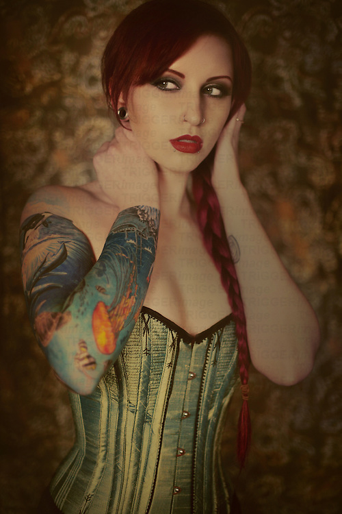 A pretty young causasian woman with bright red hair and tattoos on her arms wearing a green corset