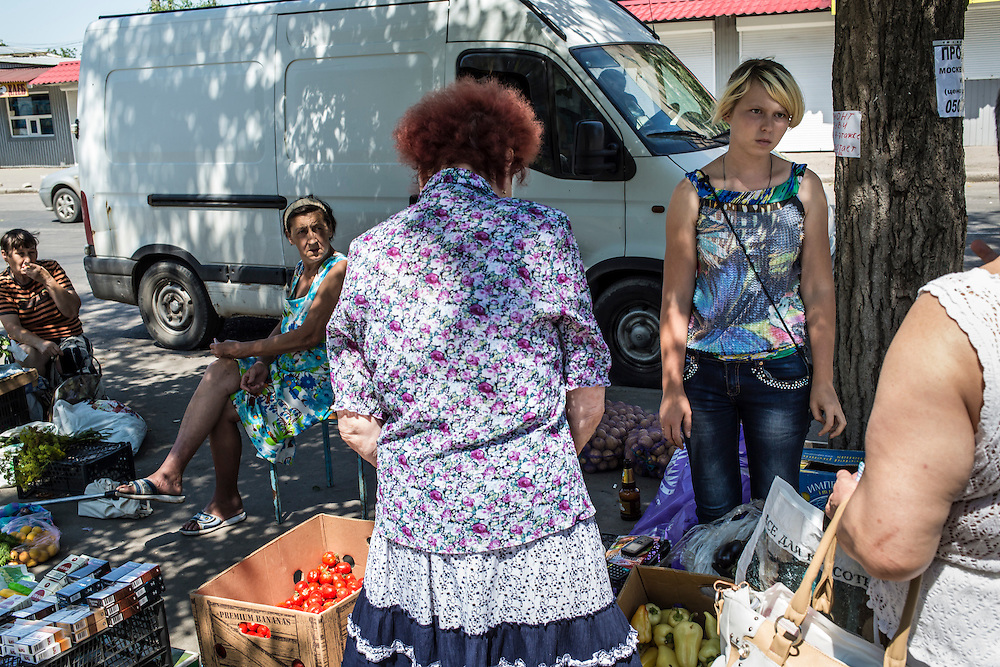 Women buy and sell vegetables on a street corner in the Oktyabrskaya neighborhood, where most shops have closed, on Sunday, July 27, 2014 in Donetsk, Ukraine.