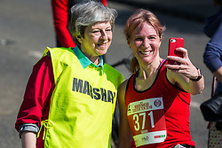 Maidenhead, UK. 19th April, 2019. A runner takes a selfie with Prime Minister Theresa May as she serves as a marshal at the annual Maidenhead Easter 10 charity race on Good Friday.