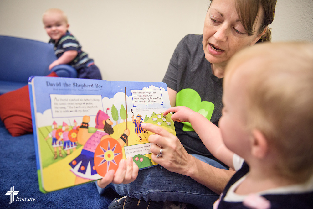 Caregiver and teacher Laurie Harkey reads a Bible story to Aleah as her brother Zayden listens in the background at ACTS of Love Early Childhood Education Center on Wednesday, Nov. 16, 2016, in Leander, Texas. LCMS Communications/Erik M. Lunsford
