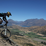 Thomas Mathews from Christchurch in action during the New Zealand South Island Downhill Cup Mountain Bike series held on The Remarkables face with a stunning backdrop of the Wakatipu Basin. 150 riders took part in the two day event. Queenstown, Otago, New Zealand. 9th January 2012. Photo Tim Clayton