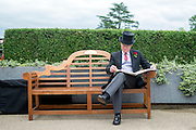 © Licensed to London News Pictures. 18/06/2014. Ascot, UK. A man reads a paper.  Day two at Royal Ascot 18th June 2014. Royal Ascot has established itself as a national institution and the centrepiece of the British social calendar as well as being a stage for the best racehorses in the world. Photo credit : Stephen Simpson/LNP