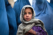 Kabul: A young girl waits in line with her mother at a UNHCR  distribution event at Tamir Mill Bus site...UNHCR distributes charcoal and NFI's to registered IDP's at one of Kabul's Informal Settlement Sites in the city centre...57 families eek out a living in a dilapidated warehouse building owned by the Ministry of Transportation. The site originally served as a storage facility for the national bus company...Tajik and Pashtun families live side by side without any major conflict. Over 70% of the families are returnees from the period 2002-2004 who are unable to achieve sustainable reintegration in their places of origin and subsequently drifted to Kabul City in search of work...There is a nearby school which is accessible to the children but the poor economic circumstances of the many families oblige them to send their children out to work. low levels of literacy, particularly amongst the women, limit their access to employment other than the lowest paid daily wage labor...Afghanistan. /UNHCR/Jason Tanner/February 2011
