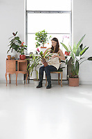 Woman tending plants by window surrounded by potted plants