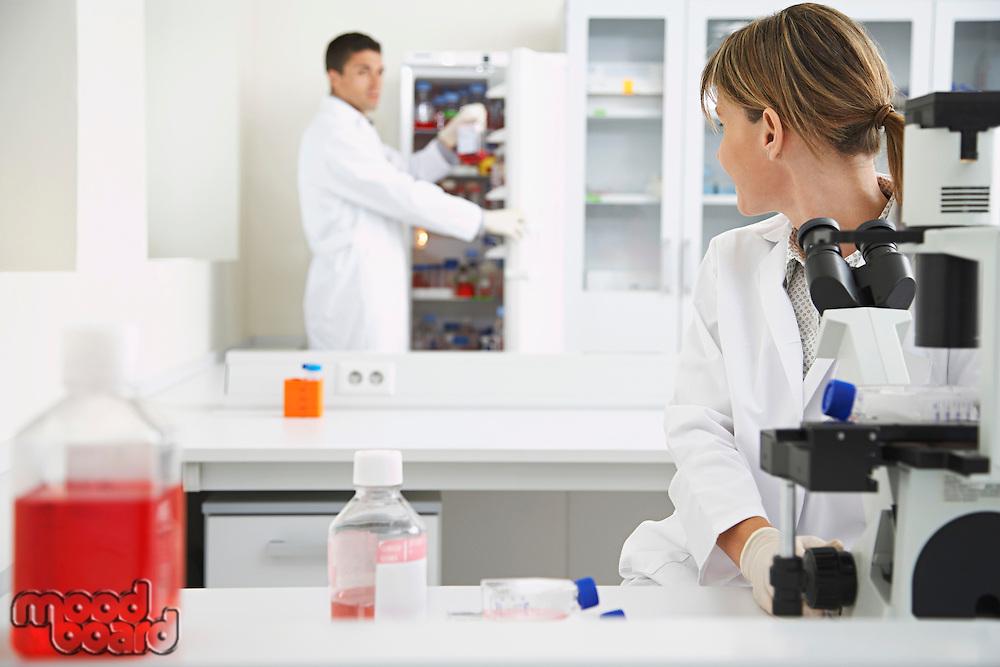 Scientist using microscope with second scientist getting specimen in laboratory