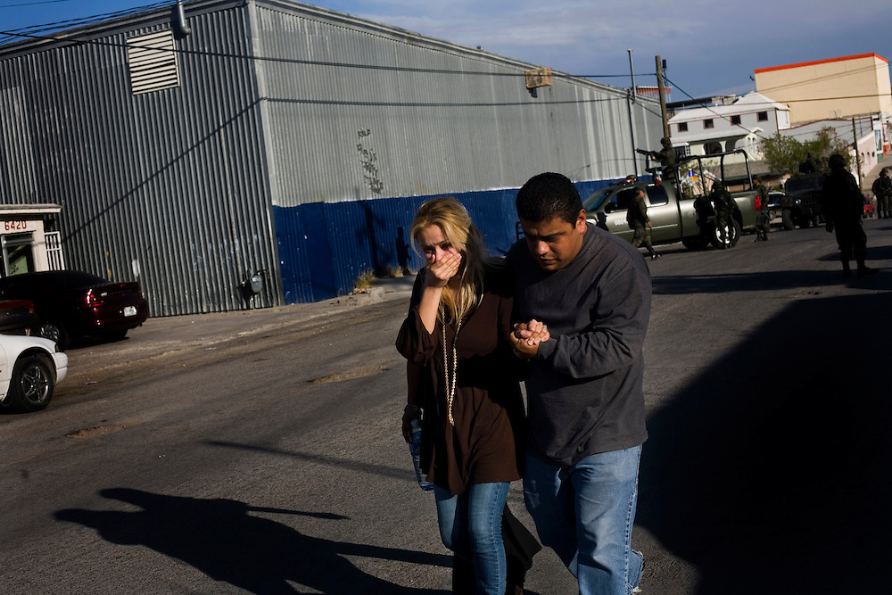 Two people leave the scene of the murder of one of their family members in Ciudad Juarez, Mexico.  Mexico is undergoing a violent war with the nation's drug cartels and Ciudad Juarez has become the murder capital of Mexico, with over 4,000 murders in the past two years.  President Felipe Calderon has dispatched thousands of soldiers and federal police officers in order to contain the situation, but they have not been successful.