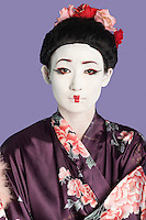 Portrait of Japanese woman in kimono with painted face against purple background