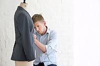Tailor working on jacket in studio