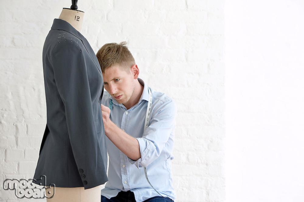 Tailor working on jacket in studio