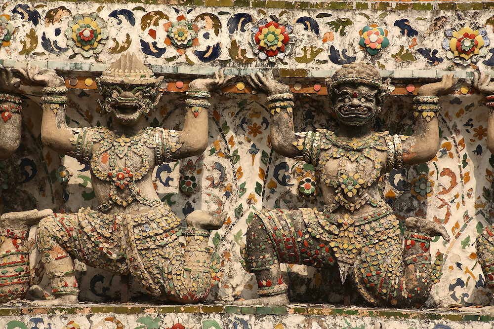 Detail of two kneeling caryatid figures on the Wat Arun, Bangkok, made from ceramic scraps and shards.