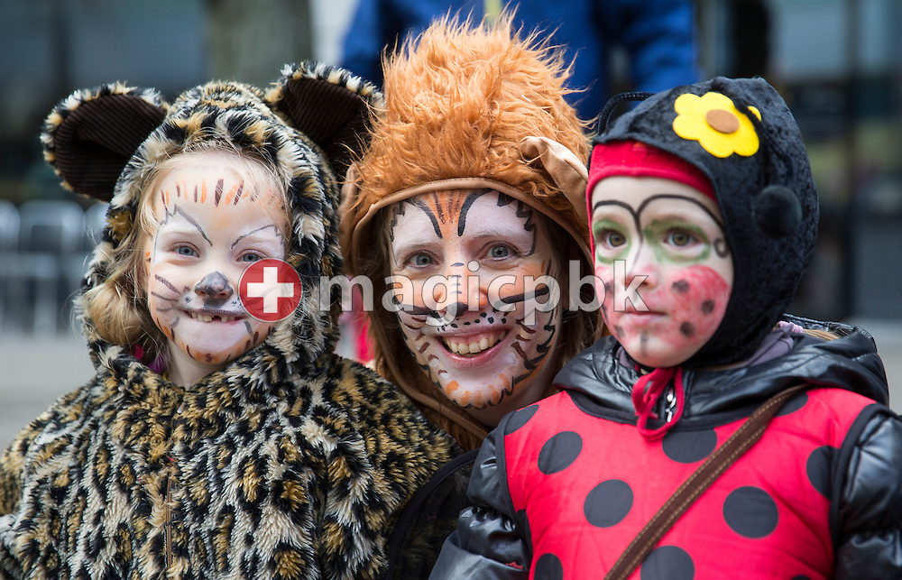 A woman and two children pose for a photo at the traditional carnival parade of the carnival in Zurich, Switzerland, Sunday, Feb. 17, 2013. (Photo by Patrick B. Kraemer / MAGICPBK)