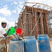CAPTION: At its peak, there were 120 people working on site, with all of the work being done via manual labour. As families live nearby, the project created jobs that according to Malawian custom are especially suited for women, such as landscaping and water fetching. LOCATION: Eco-Bricks (Mthyoka), Lilongwe, Malawi. INDIVIDUAL(S) PHOTOGRAPHED: Mphatso Madzi (left) and Rute Chinere (right).