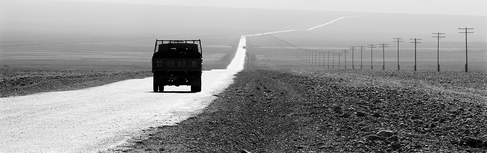 Truck traveling down long road across desert