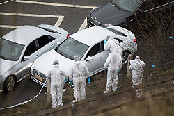© Licensed to London News Pictures. 03/01/2017. Huddersfield, UK. Forensic scenes of crime officers around a bullet riddled silver Audi car at the slip road at Junction 24 of the M62 motorway in Huddersfield . West Yorkshire police have announced a man has died following the discharge of a police firearm , during what they describe as a pre-planned operation , yesterday evening (2nd January 2017) . Photo credit : Joel Goodman/LNP