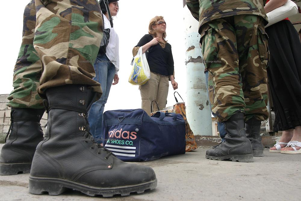 Grenzgänger werden kontrolliert. Ein Checkpoint georgischer Truppen an der Grenze zur international nicht anerkannten Republik Süd-Ossetien. Als die Sowjetunion Anfang der 1990er zerfiel, erklärte sich Süd-Ossetien unabhängig und spalte sich von Georgien ab. Den anschliessenden Krieg gewannen die Süd-Osseten. Seit dem kommt es immer wieder zu bewaffneten und unbewaffneten Zwischenfällen. Military checks civilians while they want to cross the border of South-Ossetia. A checkpoint of the georgian military at the borderline of the unrecognized Republic of South-Ossetia. During the breakdown of the Sowjet-Union South-Ossetia split off Geogia and declared itself as independent. They won the following war between them and Georgia. South-Ossetia is an international unrecognized state.