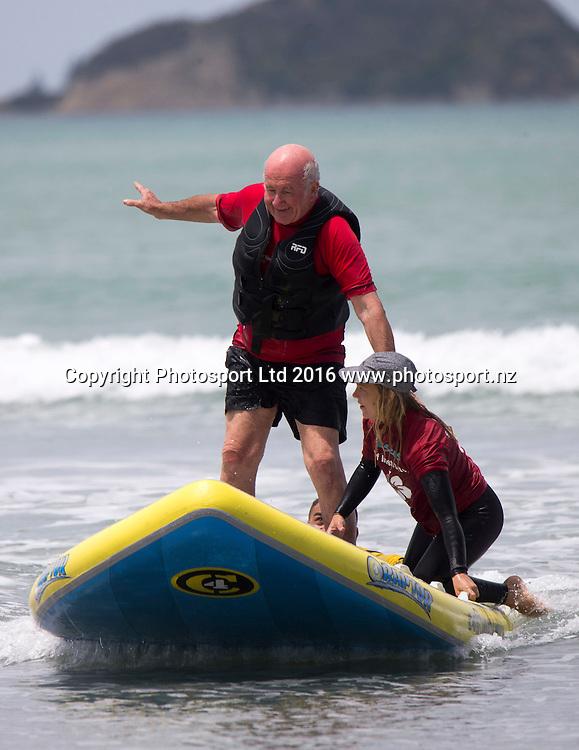 Pete Roberts has a go at surfing with Emma Lehtinen and Jane Alice from Hibiscus Surf school. Flight Centre Foundation Halberg Water Sports Day, Waikanae Beach, Gisborne, New Zealand. Saturday, 26 November, 2016. Copyright photo: John Cowpland / www.photosport.nz