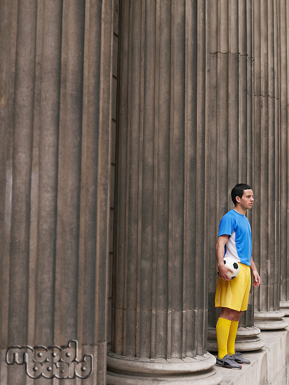 Soccer player holding ball standing between columns side view