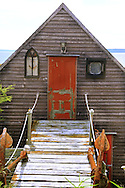 the front of a house with a orange door Scenic view of Digby, Nova Scotia Harbor on the Bay of Fundy with Scallop, Lobster,Halibut and Cod fishing boats common in the upperAtlantic coast.