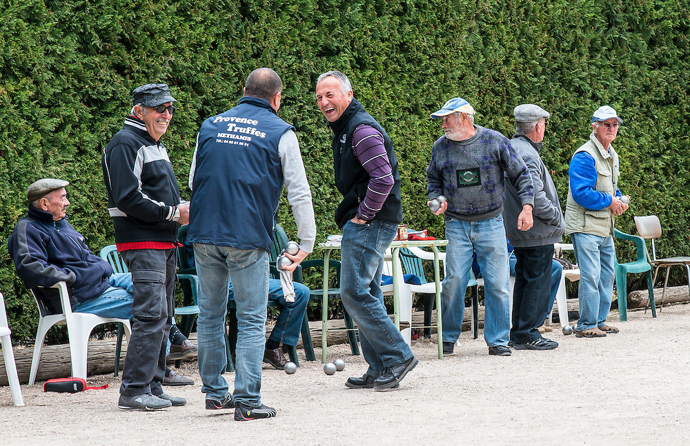 "In French, ""The Joy of living"". The photograph  captures a moment  of the petanque game's  bystanders. We can see that the men in the forground enjoy each other company. The man on the left seems to be content just sitting - doing nothing. Petanque is a popular French game played at a leisurely pace."