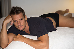 handsome man in his underwear and tee shirt in bed