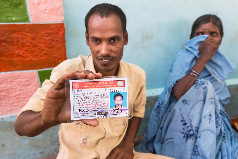 CAPTION: Visually impaired self-help group (SHG) member Shivaraju proudly displays the bus pass that his membership of the group has helped him to secure. LOCATION: Amchawadi (village), Haradanahalli (hobli), Chamrajnagar (district), Karnataka (state), India. INDIVIDUAL(S) PHOTOGRAPHED: Left: Shivaraju; right: Madamma.