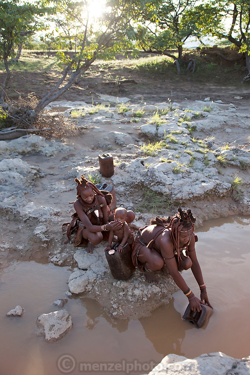 Viahondjera fetches water from a shallow, muddy river near her father's village in northwestern Namibia as her father's third wife, Mukoohirumbu, cleans her baby's face. (From the book What I Eat: Around the World in 80 Diets.) After filling up their containers they will flip their headdresses back and carry the jugs of water home on their heads.