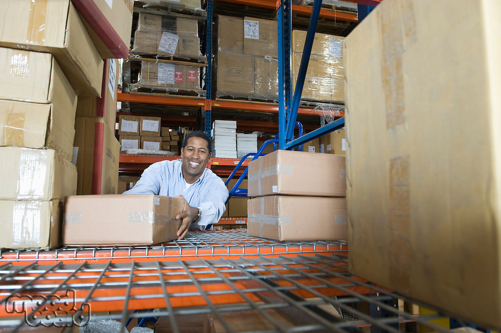 Man stacking boxes in distribution warehouse