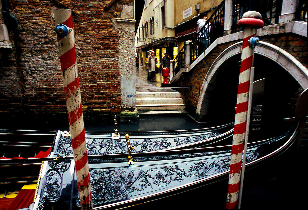 Pair of moored gondolas by a bridge over a narrow canal in the San Marco tourist district, Venice.  Shoppers visible on the street across the canal.  Two red striped mooring posts, each bearing a call bell,  frame the elaborately carved black wooden bows of the two gondolas.