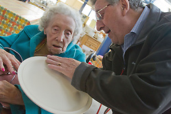 Visually impaired people with carers on outing to Denby Pottery. Feeling unglazed plate.