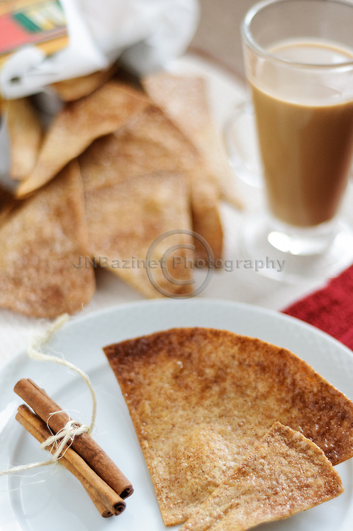 Homemade cinnamon tortilla chips with coffee.  Cinnamon tortilla crisps with cinnamon sticks and hot cup of coffee