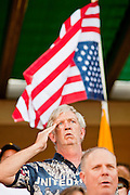 "May 29 - TEMPE, AZ: A man salutes during the Pledge of Allegiance while standing under an upside down American flag during a rally against illegal immigration in Tempe, AZ, Saturday. The upside down flag is used as a maritime symbol of a ship in distress. About 3,000 people attended a ""Buy Cott Arizona"" rally at Tempe Diablo Stadium in Tempe, AZ Saturday night. The rally was organized by members of the Arizona Tea Party movement to show support for Arizona law SB1070. The ""Buy Cott"" is a reaction to the economic boycott planned by opponents of SB1070. SB1070 makes it an Arizona state crime to be in the US illegally and requires that immigrants carry papers with them at all times and present to law enforcement when asked to. Critics of the law say it will lead to racial profiling, harassment of Hispanics and usurps the federal role in immigration enforcement. Supporters of the law say it merely brings Arizona law into line with existing federal laws.  Photo by Jack Kurtz"