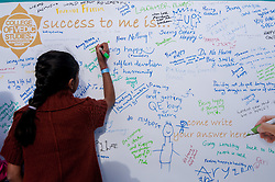 © Licensed to London News Pictures. 05/09/2015. Watford, UK. A girl writes on a whiteboard encouraging visitors to leave their responses to the question during their visit to the biggest Janmashtami festival outside of India at the Bhaktivedanta Manor Hare Krishna Temple in Watford, Hertfordshire.  The event celebrates the birth of Lord Krishna and the festival  includes music, dance, food, dramas and more. Photo credit : Stephen Chung/LNP