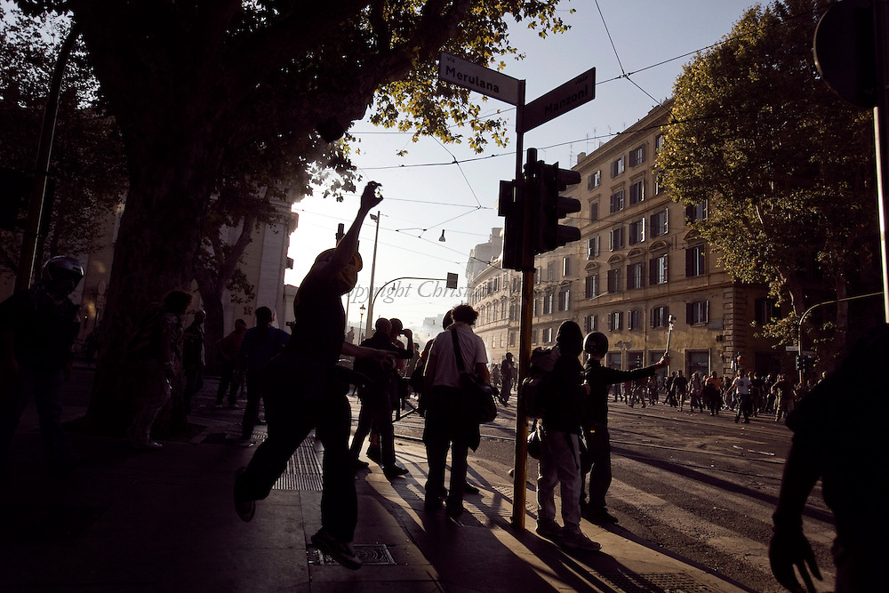 ITALY, Rome, October 15, 2011:  A protester throws a stone against police officers during a demonstration in Rome on October 15, 2011. © Christian Minelli/Emblema.