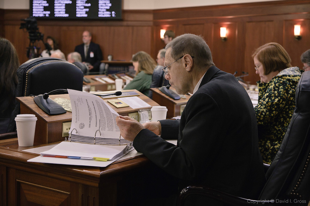 Rep. Carl Gatto (R) reads through a bill in the Alaska State House of Representatives.