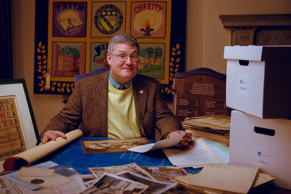 Dr. David Califf, instructor of English, Classics and the History of Art, as well as Keeper of the Archives at Notre Dame Academy de Namur, sits at a desk replete with artifacts from the schools history, dating back to the mid 19th century.