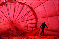 © Rob Arnold.  31/07/2014. Hampshire, UK. The pilot of a hot air balloon prepares to take a group of people on a flight from Basingstoke in Hampshire. The balloon flights depart from War Memorial Park in the centre of Basingstoke, and fly for around 2 hours to wherever the wind takes them. Photo credit : Rob Arnold