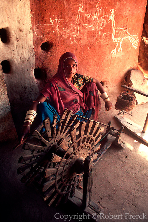INDIA, VILLAGE LIFE Rajasthan; woman spinning wool for weaving in rural village home