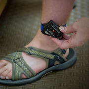 ROCKVILLE, MD - JUL25: Barbara Bucknam checks the battery on her son John's ankle tracking device, at their home in Rockville, MD, July 25, 2014. John, 18,  has autism, and wears a tracking device on his ankle so he can be found in case he wanders away from home. The Bucknam's have a series of locks on their doors to keep John from wandering off. (Photo by Evelyn Hockstein/For The Washington Post)