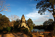Built around 1190 AD by King Jayavarman VII, Angkor Thom is built on a north-south axis. Here, the South Gate, adorned by portraits of the King himself, as approached across a causeway flanked by giant rower statues. Angkor Thom, Cambodia