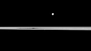 Saturn's small moon Prometheus appears embedded within the planet's rings near the center of this Cassini spacecraft view while the larger moon Mimas orbits beyond the rings.