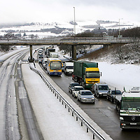 Lorries and cars queueing as far as the eye can see on the southbound M90 at Junction 6 Kinross in Perthshire after snow caused traffic chaos. The northbound carriageway is deserted as the motorway was closed and blocked.<br />