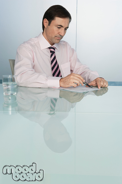 Business man writing at table in conference room