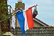 Nederland, Groesbeek, 2-7-2016 Vlag met boekentas is uitgehangen om te vieren dat het eindexamen is gehaald. Deze week hebben scholieren van het voortgezet onderwijs de uitslag van hun eindexamen gekregen. Bij veel geslaagden gaat traditioneel de vlag uit, met de schooltas aan het einde van de stok. Foto: Flip Franssen