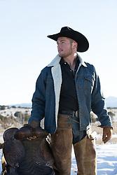 cowboy holding a saddle outdoors