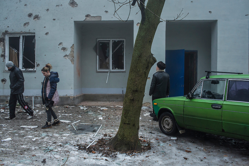 DONETSK, UKRAINE - JANUARY 30, 2015: People examine the outside of an apartment building scarred when a rocket or mortar landed just outside in Donetsk, Ukraine. At least two people were killed on the sidewalk when another shell landed just around the corner, and at least five died when a shell landed in the parking lot of a nearby humanitarian aid distribution center. CREDIT: Brendan Hoffman for The New York Times