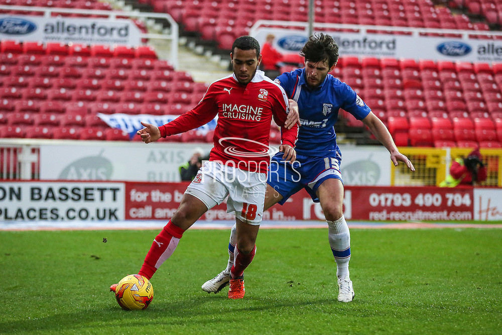 Swindon Town's Louis Thompson and Gillingham's Aaron Morris tussle for the ball during the Sky Bet League 1 match between Swindon Town and Gillingham at the County Ground, Swindon, England on 26 December 2015. Photo by Shane Healey.