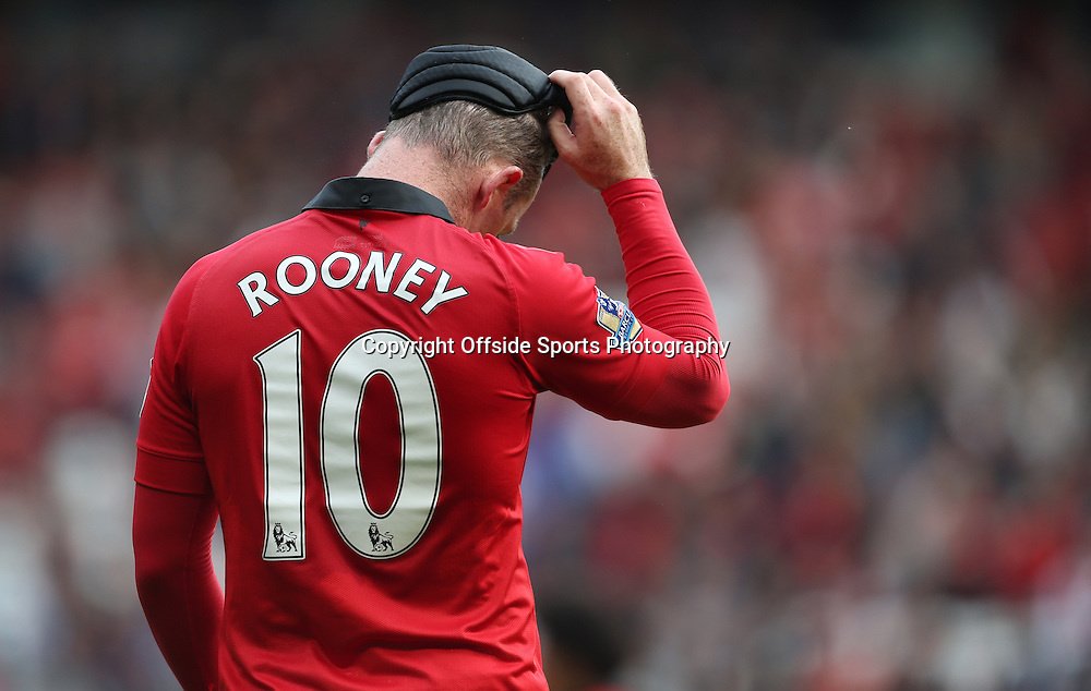 14th September 2013 - Barclays Premier League - Manchester United v Crystal Palace - Wayne Rooney of Man Utd removes his protective headband at the end of the match - Photo: Simon Stacpoole / Offside.