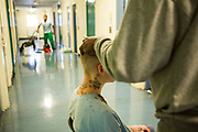 An inmate has his hair cut in the corridor of Beaufort House, a skill development unit for enhanced prisoners. Part of HMP/YOI Portland, a resettlement prison with a capacity for 530 prisoners. Dorset, United Kingdom.