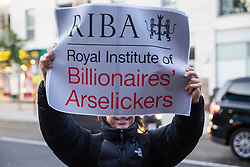 London, UK. 8 October, 2019. A supporter of Architects for Social Housing (ASH) holds up a poster during a protest outside the award ceremony for the Riba Stirling Prize at the Roundhouse. ASH were protesting against the Royal Institute of British Architects' (RIBA) nomination of the architecture of social cleansing, estate demolition and housing privatisation for the Stirling Prize, against the false promotion of council-owned commercial housing development and management companies as a so-called 'renaissance in social housing' and against the association of the name of socially committed architect, the late Neave Brown, with the architecture of Neo-liberalism. Credit: Mark Kerrison/Alamy Live News